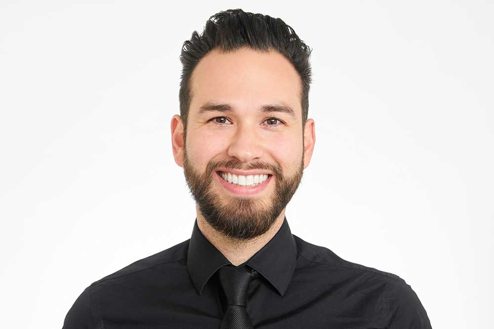 man smiling with black collared shirt and tie for his professional headshots