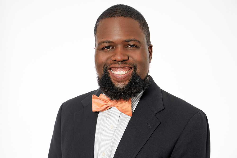 man with orange bow tie smiling for his professional headshots
