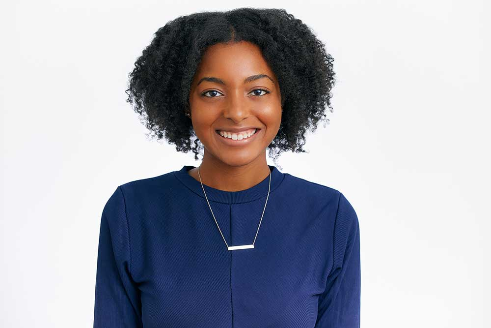 young woman in blue blouse smiling for her professional headshots