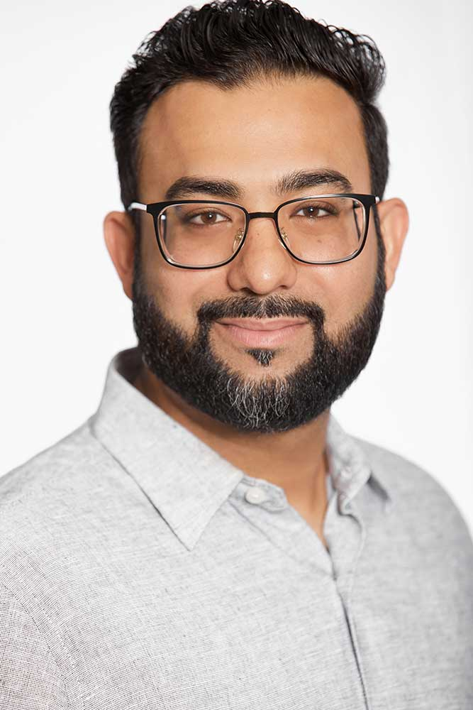 man with beard and glasses smiling for his professional headshots