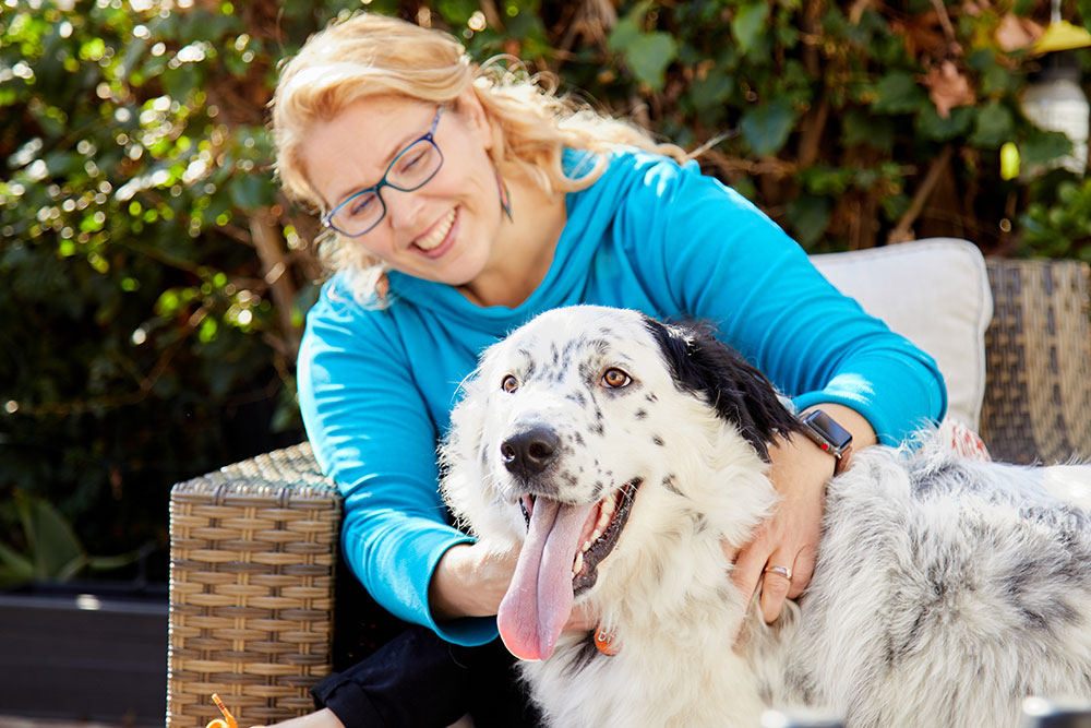 woman in blue shirt petting dog business photography